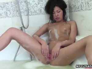 Playful Asian girl with small boobs takes bubble bath